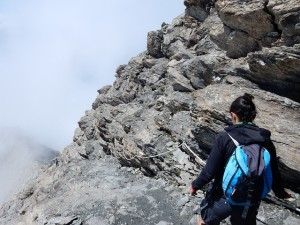 A woman hiker with a blue backpack on a rocky mountain trail.